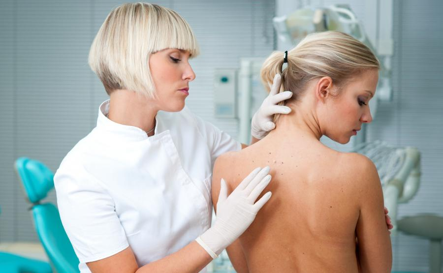 Lekarz dermatolog ogląda skórę na plecach pacjentki