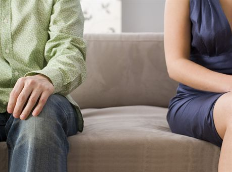 Mid section view of a man and a woman sitting on a couch