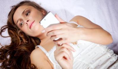 Kobieta w łóżku z telefonem