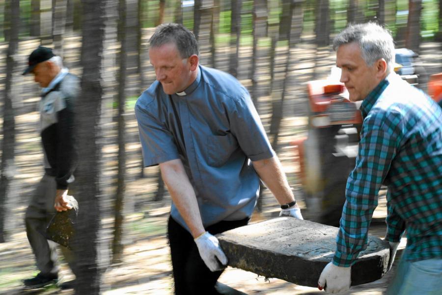 Ksiądz Wojciech Lemański przenosi macewy z podwórza plebanii na cmentarz żydowski. W czasie wojny Niemcy wybrukowali nagrobkami podwórze posterunku żandarmerii w miejscowości Sobienie-Jeziory. Po wojnie podwórze posterunku stało się podwórzem plebanii