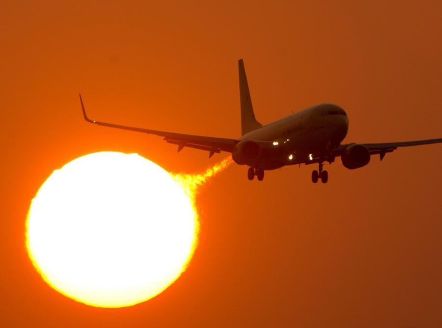 Startujący boeing 737 na tle słońca