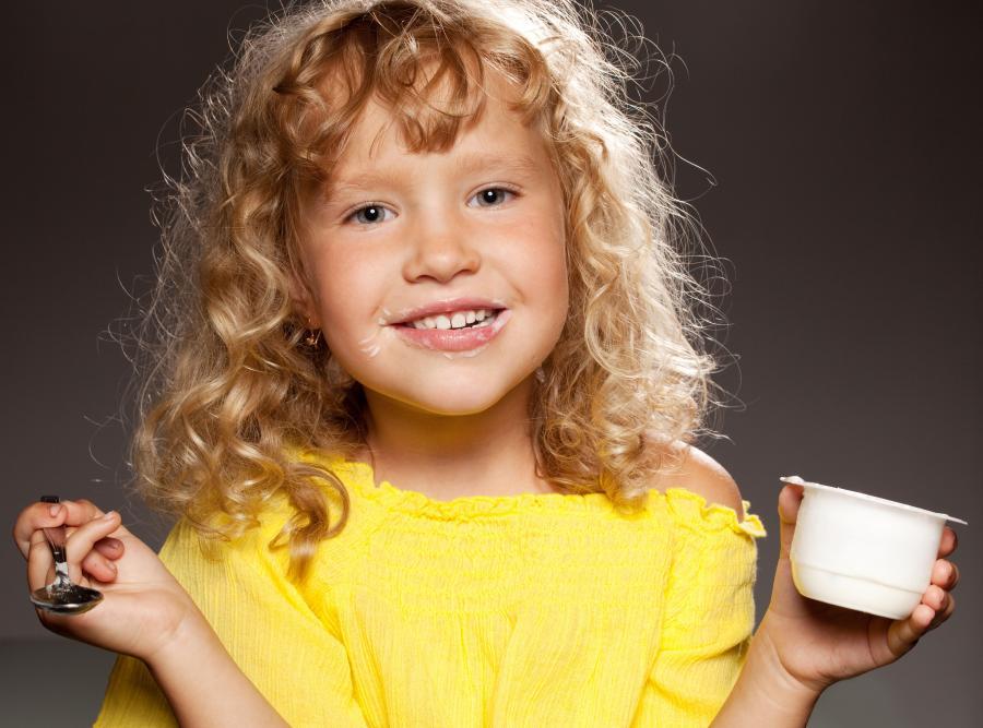 Dziewczynka je jogurt