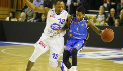 Danny Gibson (L) z ROSA blokuje kozłującego piłkę Rodneya Blackmona (P) z Polpharmy, podczas meczu Tauron Basket Ligi koszykarzy, ROSA Radom -Polpharma Starogard Gdański