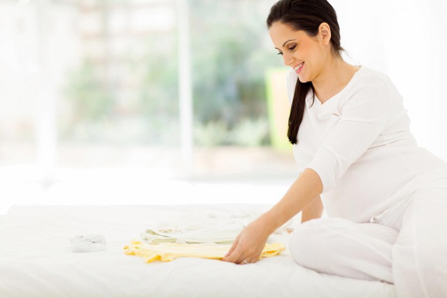 Kobieta w ciąży oglądająca ubranka dla dziecka