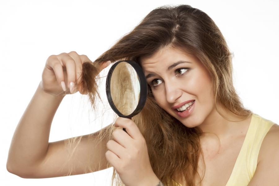 Kobieta oglądająca swoje włosy