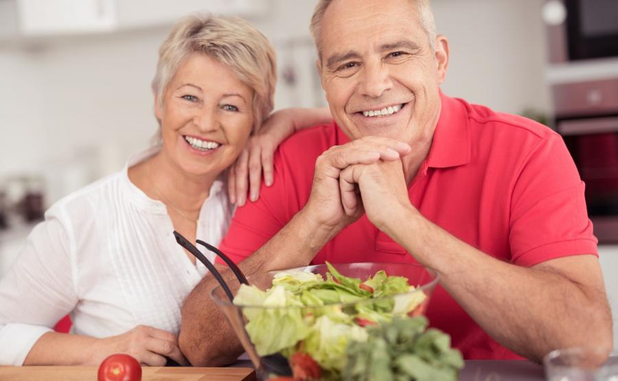 Starsza kobieta i starszy mężczyzna szykują posiłek