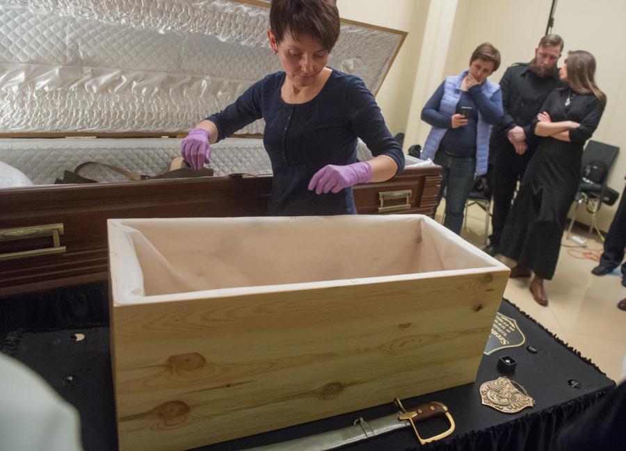 Antropolog dr Zofia Łubocka przekłada szczątki do trumny